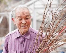 笑顔で花に接する故・阿部一郎氏